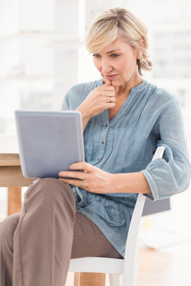 Woman looking at tablet in a chair at an office desk with windows in the background